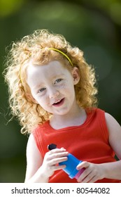 Cute little red haired girl holding bubble wand.