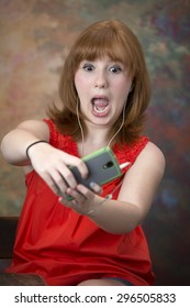Cute little red head teen girl with a surprised look while viewing her cell phone