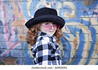 Cute little redheaded girl in black hat and pink glasses  in front of brightly painted brick wall