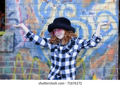Cute little redheaded girl in black hat and pink glasses with arms up and showing expression  in front of brightly painted brick wall