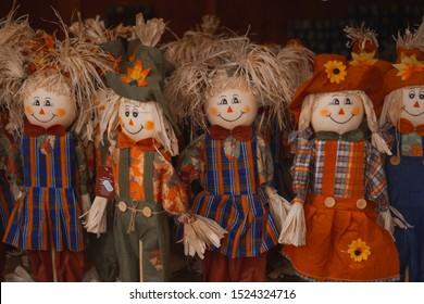 Cute little scarecrow ( straw man ) handmade toys for decoration or play. Seasonal farm decor elements for Halloween, Thanksgiving, Autumn Celebration. Selective focus.