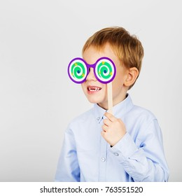 Cute little school boy with funny paper glasses against a white background. Cheerful smiling Kid with funny photo props. School concept. Back to School. Child's toothless mouth
