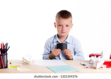 Cute little school boy with sad face sitting at his desk on white background.Unhappy intelligent children in shirt with blue eyes