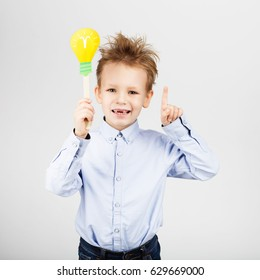 Cute little school boy with yellow paper lightbulb against a white background. Cheerful smiling Kid with funny photo props. School concept. Back to School. Child's toothless mouth