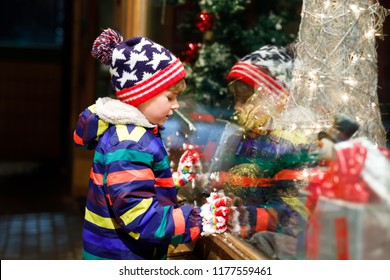 Cute little school kid boy on Christmas market. Funny happy child in fashion winter clothes making window shopping decorated with gifts, xmas tree. holidays, christmas, childhood and people concept