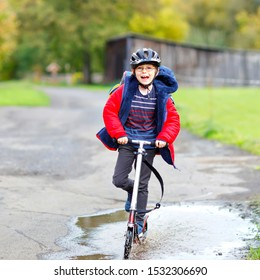 cute little school kid boy riding on push scooter on the way to or from school. Schoolboy of 7 years driving through rain puddle. funny happy child in colorful fashion clothes and with helmet.