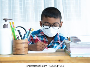 Cute little schoolboy boy studies at home