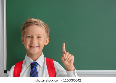 Cute little schoolboy with raised index finger near blackboard in classroom