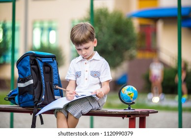 Cute little schoolboy studying outdoors on sunny day. Young student doing his homework. Education for small kids. Back to school concept.