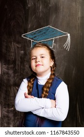 cute little schoolgirl against chalkboard, with drawn square academic cap
