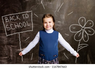 cute little schoolgirl against chalkboard, with drawn flower and plate back to school
