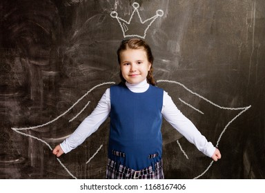 cute little schoolgirl against chalkboard, with drawn crown and cloak