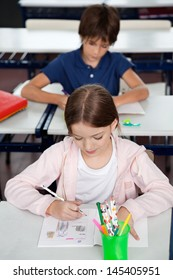 Cute little schoolgirl drawing at desk with male friend sitting in classroom