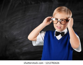 Cute little schoolgirl in glasses on blackboard background