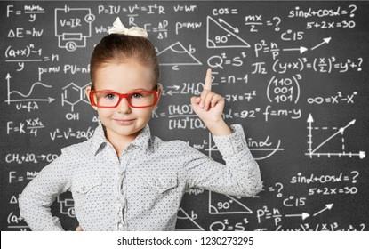 Cute little schoolgirl in glasses on blackboard background