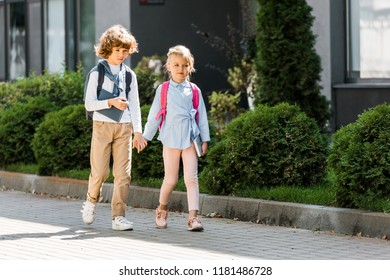 cute little schoolkids with backpacks holding hands and walking together on street