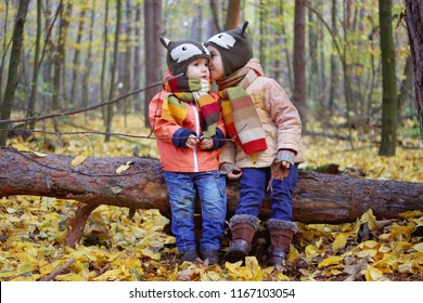 Cute little siblings in the same funny hats walking and having a rest in the beautiful autumn forest, autumn outdoor, warm family weekend concept