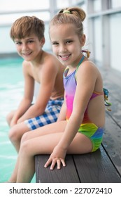 Cute little siblings sitting poolside at the leisure center