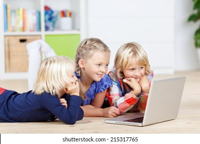 Cute little siblings using laptop while lying on floor at home