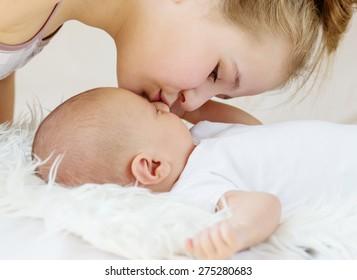 Cute little sister kisses newborn brother