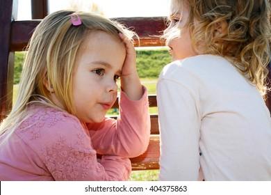 Cute little sisters gossip in the backyard.