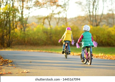 Cute little sisters riding bikes in a city park on sunny autumn day. Active family leisure with kids. Children wearing safety helmet while riding a bicycle.