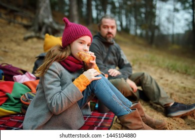 Cute little sisters and their father having picnic by a bonfire on cold autumn day. Children having fun at camp fire. Camping with kids in fall forest. Family leisure with kids at autumn.