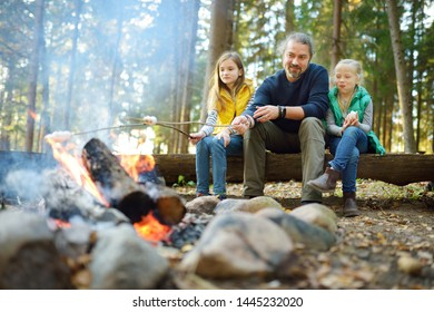 Cute little sisters and their father roasting marshmallows on sticks at bonfire. Children having fun at camp fire. Camping with kids in fall forest. Family leisure with kids at autumn.