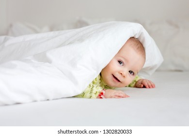 Cute little six month old baby boy, playing under duvet at home in bed in bedroom, smiling happily