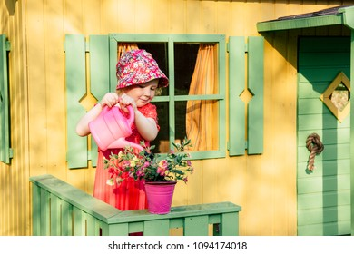 Cute little smiling gardener girl wearing floral summer hat watering pretty pink flowers with pink watering can in front of a playhouse.