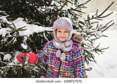 Cute little smiling girl with christmas tree. Family, tradition, celebration concept