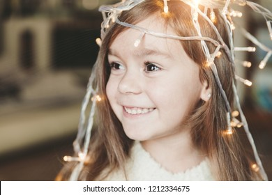 Cute little smiling girl with christmas luminous garland on her head. Christmas holiday portrait of happy child.