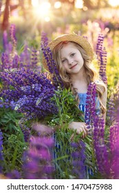 Cute little smiling girl in the lupinus field with purple flower in spring
