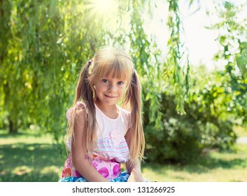 Cute little smiling girl in the park