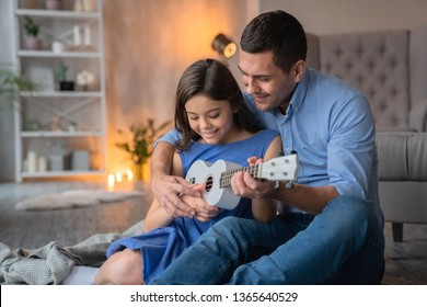 Cute little smiling girl playing on ukulele guitar with her father. Happy father teaching to play on ukulele guitar his daughter at home