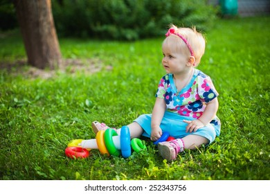 A cute little smiling girl playing in the meadow in a sunny summer day