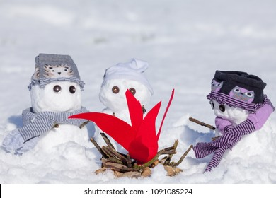 Cute little snowmen dressed for winter, huddled around a camp fire trying to keep warm. Snow covered scene in Norfolk UK. Snowman wearing clothes.