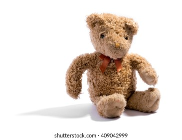 Cute little soft brown stuffed plush teddy bear wearing a bow-tie sitting on white with copy space