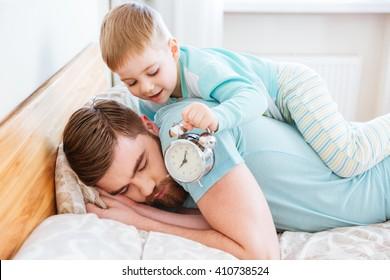 Cute little son holding alarm clock near sleeping father ear at home