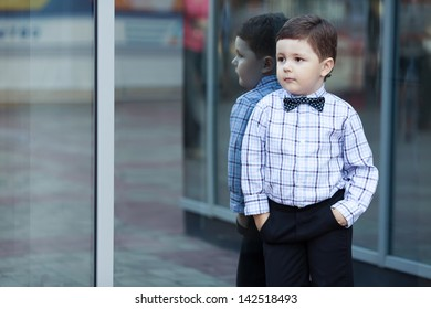 cute little stylish boy in classic style in the city close to the shop window