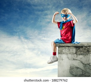 Cute little superhero boy with raised fists and blue sky on background.