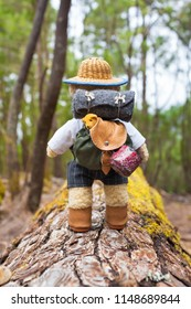 Cute little teddy bear backpacker travels with vintage miniature equipment along tree trunk through forest