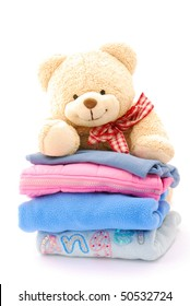 A cute little teddy bear looking over a stack of colorful kids clothes. Image isolated on white studio background.