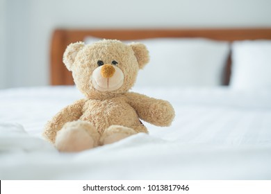 Cute little teddy bear sitting alone on white bed in morning.