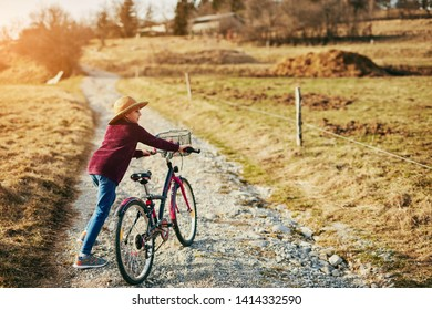 Cute little ten year old girl riding bicycle on countryside.