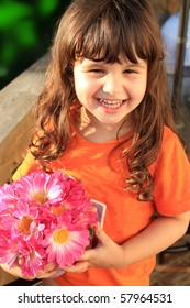 Cute little three year old girl smiling and holding pink flowers