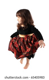Cute little three year old girl in a fancy plaid and velvet dress dancing on a white background