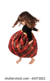 Cute little three year old girl in a fancy plaid and velvet dress dancing and twirling on a white background with selective focus and motion blur