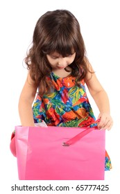 Cute little three year old girl looking to see what's in the  pink shopping back on a white background