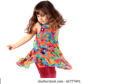 Cute little three year old girl in a flower dress dancing on a white background
